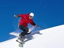 Der Snowboarder springend durch Luft mit tiefem blauem Himmel Lizenzfreie Stockfotos