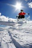 der Snowboarder springend gegen blauen Himmel Lizenzfreies Stockbild