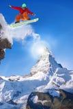 Der Snowboarder springend gegen Matterhorn-Spitze in der Schweiz Stockbild