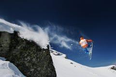Der Snowboarder springend von einer Klippe Lizenzfreies Stockbild