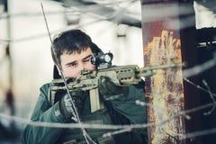 Der Soldat, der ein Gewehr hält und zielen auf den Feind lizenzfreies stockfoto
