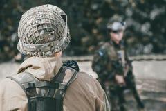 Der Soldat in der Leistung von Aufgaben in der Tarnung, im Sturzhelm und im Halten eines Maschinengewehrs, im Hintergrund gesehen stockbild