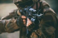Der Soldat in der Leistung von Aufgaben in der Tarnung, in Schutzhandschuhen, in Sturzhelm und in abgetönten Gläsern, die ein Mas lizenzfreie stockfotografie