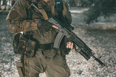 Der Soldat in der Leistung von Aufgaben in der Tarnung und in Schutzhandschuhen, die ein Gewehr halten lizenzfreie stockfotografie