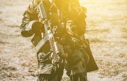 Der Soldat in der Leistung von Aufgaben in der Tarnung und in Schutzhandschuhen, die ein Gewehr halten stockbilder