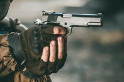 Der Soldat in der Leistung von Aufgaben in der Tarnung und in Schutzhandschuhen, die eine Pistole mit dem gespannten Hammer halte lizenzfreies stockfoto