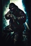 Der Soldat, der sein Gewehr mit Laser hält, schaltete ein Stockfoto