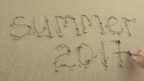 Der SOMMER 2017, der auf den Strandsand geschrieben wurde, wusch sich immer durch Wellen Stockfoto