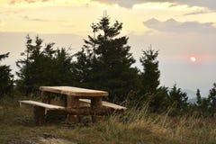 Der Sonnenaufgang in den Bergen und im Holztisch Lizenzfreie Stockfotos