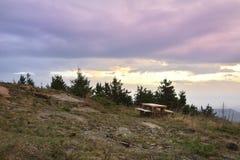 Der Sonnenaufgang in den Bergen und im Holztisch Stockbild