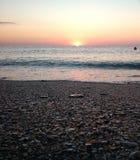 Der Sonnenaufgang, der von einem Strand gesehen wurde, hetzte durch Meereswellen Stockbilder
