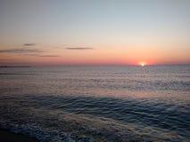 Der Sonnenaufgang, der von einem Strand gesehen wurde, hetzte durch Meereswellen Stockfoto