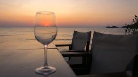 Der Sonnenaufgang durch auf dem Tisch gesehen einem Glas, mit Stühlen und Wasser des ruhigen Sees lizenzfreie stockbilder