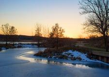 Der Sonnenuntergang, der im Eis reflektiert wurde, bedeckte Teich entlang Gehweg lizenzfreies stockfoto
