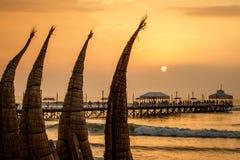 Der Sonnenuntergang mit traditionellem Bootshandwerk an Huanchaco-Stadt, Peru Lizenzfreies Stockbild