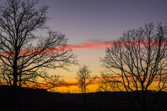 Der Sonnenuntergangplatz mit einigen einzelnen Bäumen stockfoto