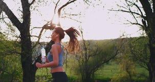 In der sonniger Tagesattraktiven jungen Dame, die mitten in Natur läuft, während das Halten ihrer Plastikflasche sie konzentriert