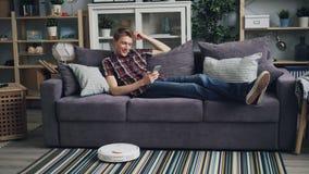 Der sorglose junge Mann dreht sich auf den Roboterstaubsauger, der dann auf Sofa sitzt und Smartphone Bequemlichkeit genießend ve stock video