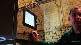 Der Spezialist nimmt Anpassungen zur Ausrüstung vor, welche die Fragen des Programms beantwortet stock video