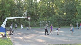 Der spielende Basketball der jungen muskulösen Männer im Park stock video footage