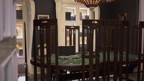 Der Spieltisch mit grüner Oberfläche mit dem Schürhaken eingestellt auf ihn im modernen Kasino, hohe hintere Stühle, die nahe ste stock video
