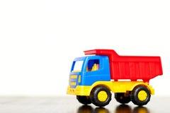 Der Spielzeuglastwagen der Kinder, ein mehrfarbiger Plastikkipplaster auf einem weißen Hintergrund, Kopienraum Spielwaren f?r Jun lizenzfreies stockfoto