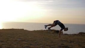 Der Sport, der in der Natur, der Athletenkerl tut leichte Schläge ausbildet, betrügt auf Flussküste gegen Himmel in der Nachglut stock video