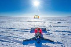Der Sportler auf einem Snowboard lässt Drachen laufen Lizenzfreies Stockfoto