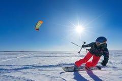 Der Sportler auf einem Snowboard lässt Drachen laufen Stockfoto