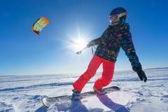 Der Sportler auf einem Snowboard lässt Drachen laufen Stockfotografie