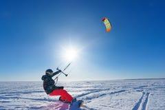 Der Sportler auf einem Snowboard lässt Drachen laufen Lizenzfreie Stockfotografie