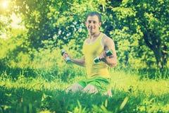 Der Sportler, der auf Gras sitzen und die anhebenden Gewichte im Park fangen ins auf Lizenzfreie Stockbilder