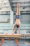 Der Sportler während der schwierigen Übung, Sportgymnastik Lizenzfreies Stockfoto