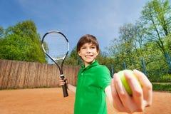 Der sportliche Junge, der Tennis beginnt, stellte auf den Sandplatz ein Lizenzfreie Stockfotos