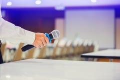 Der Sprecher hielt das Mikrofon in seiner Hand mit undeutlichem Konferenzsaal und Projektor lizenzfreie stockbilder