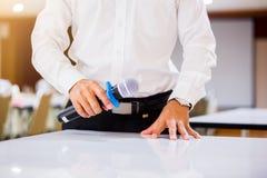 Der Sprecher hielt das Mikrofon in seiner Hand mit undeutlichem Konferenzsaal und Projektor stockfotografie