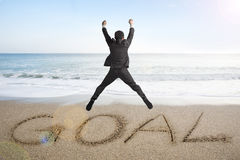 Der springende Geschäftsmann, der für Ziel zujubelt, fassen geschrieben auf Sandstrand ab Stockfotografie