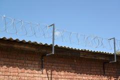 Der Stacheldraht ist über einer Backsteinmauer angespannt Stockfotos