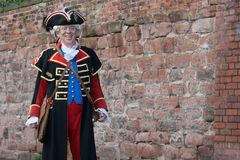 Der Stadtausrufer von Chester, England, mit einer Backsteinmauer im Hintergrund Lizenzfreie Stockbilder
