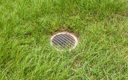 Der Stahlbodenabfluß, fließendes Wasser von der Wiese Lizenzfreies Stockfoto