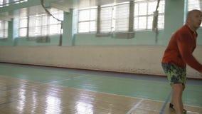 Der starke Kerl in rotem Laceball schlägt weg von der Schürzen-Schüssel mit Schläger, Spiel-Badminton stock video footage