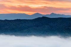 Der starke Nebel fiel unter die Berge während des Sonnenuntergangs lizenzfreie stockbilder