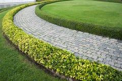 Der Steinblockwegpfad im Park mit grünem g Stockbild
