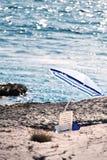 Der steinige Strand mit Sonnenschirm stockbild