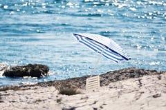 Der steinige Strand mit Sonnenschirm lizenzfreies stockfoto