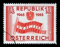 Der Stempel, der im Österreich gedruckt wird, zeigt die Buchstaben, die Flagge, 10. Jahrestag von Österreich-` s Befreiung bilden Lizenzfreie Stockfotos