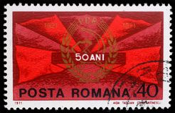 Der Stempel, der in Rumänien gedruckt wird, zeigt rote Fahnen und kommunistisches Parteiabzeichen Stockfotografie