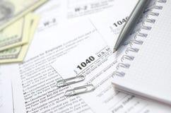 Der Stift, das Notizbuch und die Dollarscheine ist Lügen auf dem Steuerformular 1040 Stockbilder