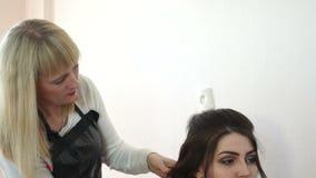 Der Stilist setzt ihr Haar in eine Frisur ein stock footage