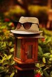 Der stilvolle Hut, Muffe, Napper mit Sonnenbrille, Schauspiele steht auf der Lampe mit warmen Tönen in Sommerzeiten stockfoto
